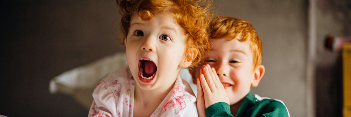 Two children with red hair laughing